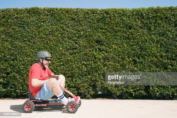 hispanic man riding child's toy - young at heart stock pictures, royalty-free photos & images
