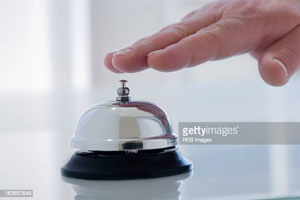 Hispanic man ringing service bell on desk