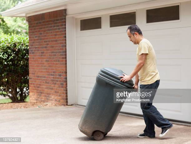 hispanic man rolling garbage can - garbage can stock photos and pictures