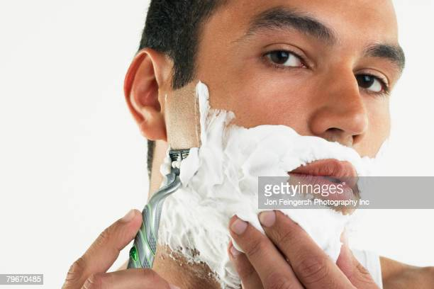 Hispanic man shaving face