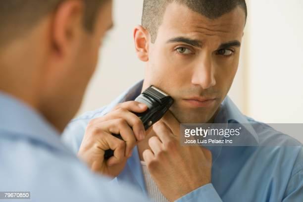 Hispanic man shaving with electric razor