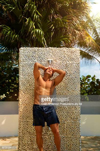 Hispanic man showering in swim trunks outdoors