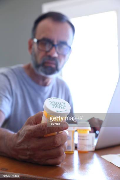Hispanic Man Sitting At Dining Room Table Looking At His Prescription Medications