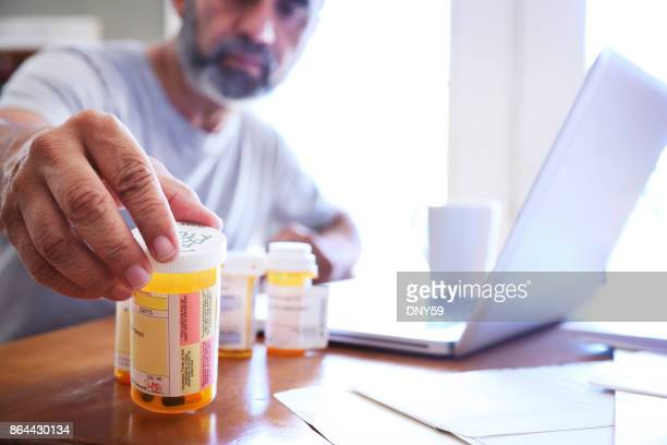hispanic man sitting at dining room table reaches for his prescription medications - moving activity stock pictures, royalty-free photos & images