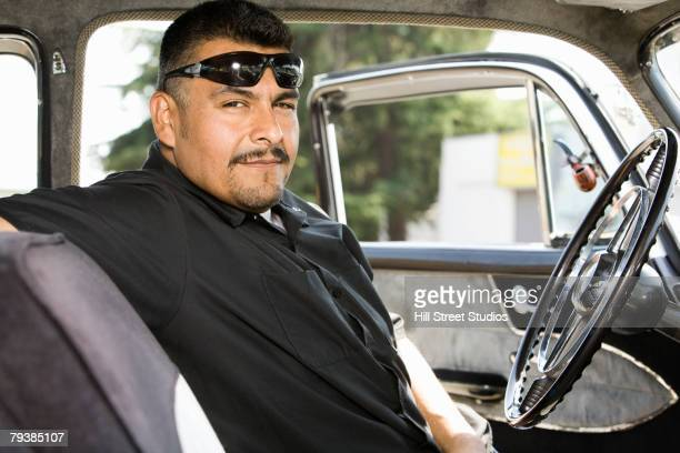 hispanic man sitting in car - low rider stock pictures, royalty-free photos & images