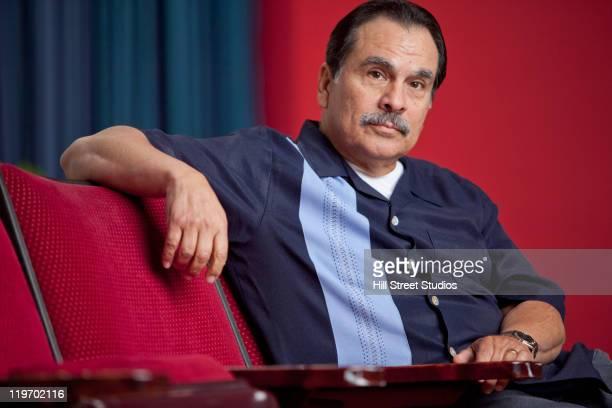Hispanic man sitting in theater