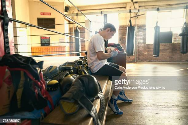 Hispanic man sitting near boxing ring wrapping hands