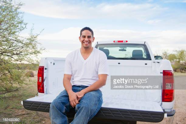 hispanic man sitting on back of pick-up truck - pick up truck stock pictures, royalty-free photos & images