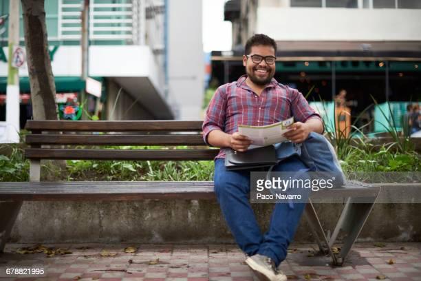 Hispanic man sitting on bench reading brochure