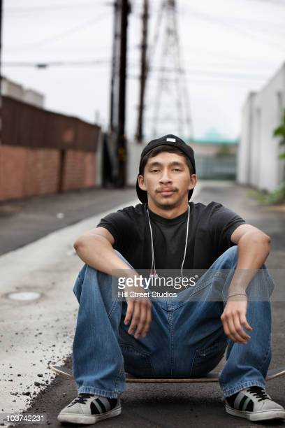 hispanic man sitting on skateboard in alley - gardena california stock pictures, royalty-free photos & images