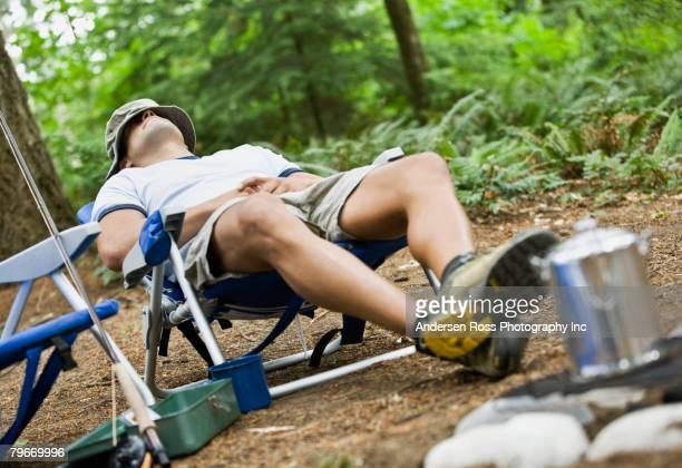 Hispanic man sleeping at campsite