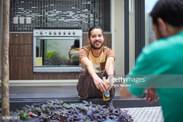 hispanic man smiling in atrium - mexican beer stock pictures, royalty-free photos & images