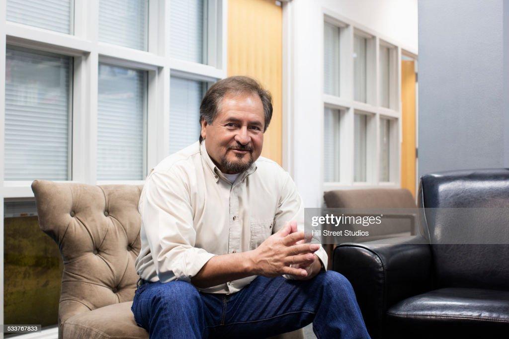 Hispanic man smiling on sofa in campus lounge : Foto stock