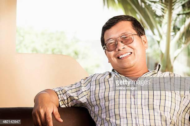 Hispanic man smiling on sofa