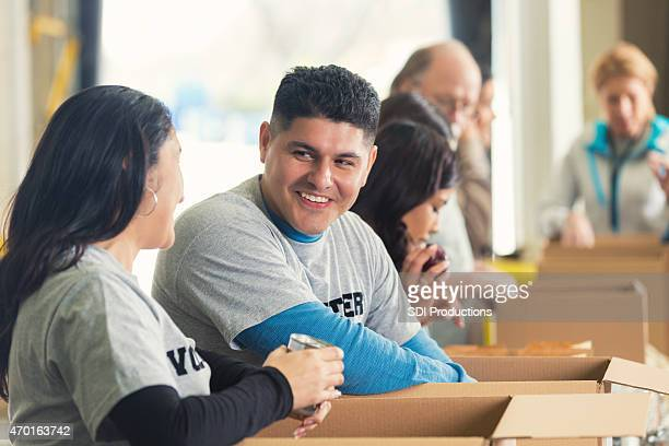 Hispanic man sorting donations in food bank with volunteers