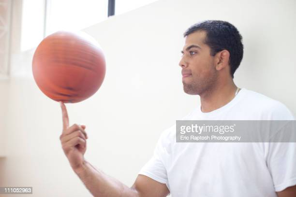 Hispanic man spinning basketball on finger