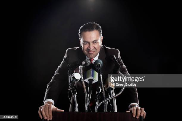 hispanic man standing at podium with microphones - 記者会見 ストックフォトと画像