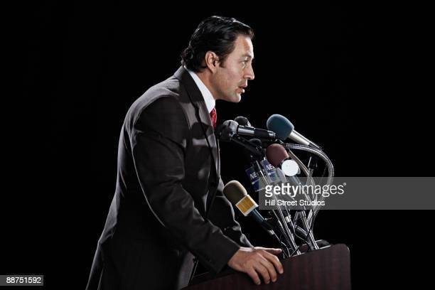 Hispanic man standing at press conference podium