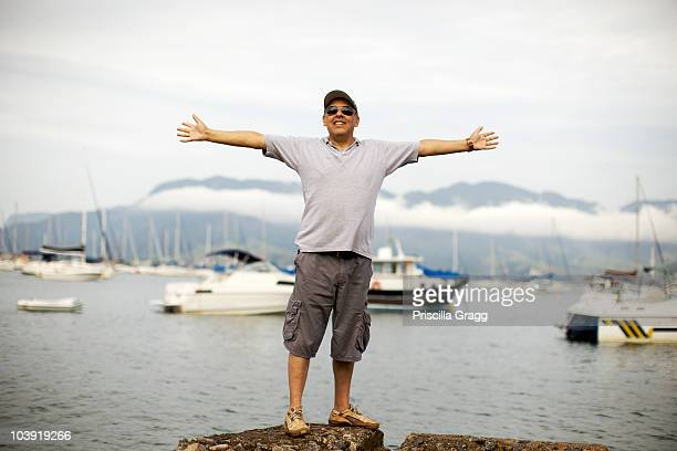 hispanic man standing at waterfront - arms outstretched stock pictures, royalty-free photos & images