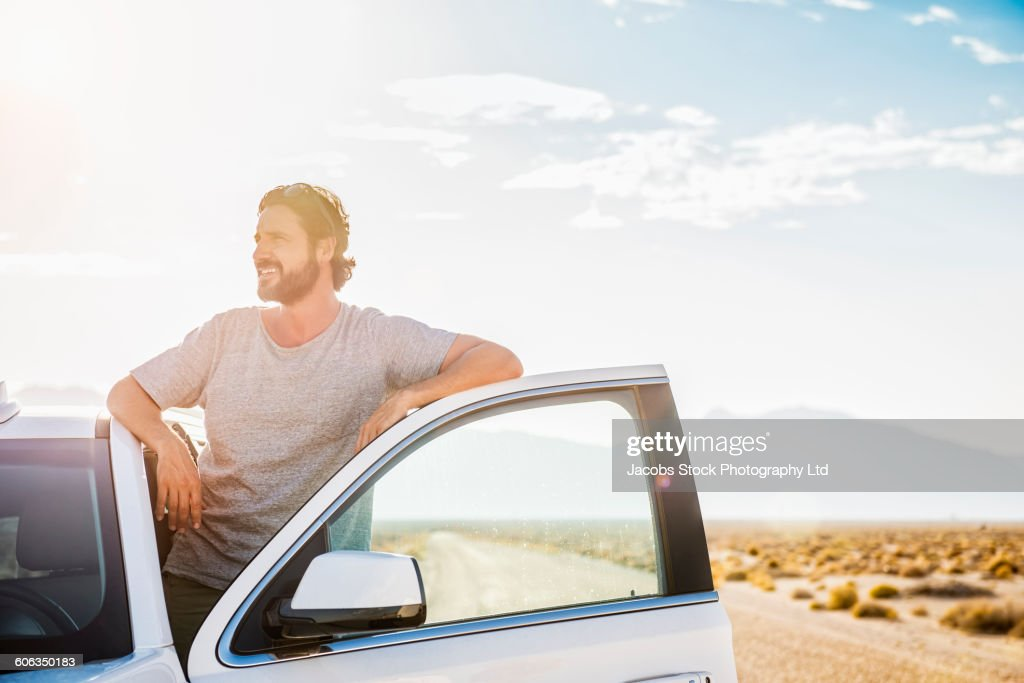 Hispanic man standing in car on remote road : Stock Photo