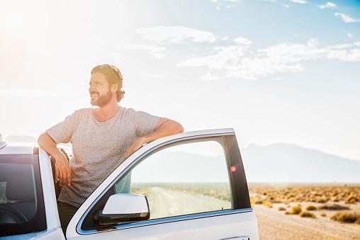 Hispanic man standing in car on remote road - gettyimageskorea