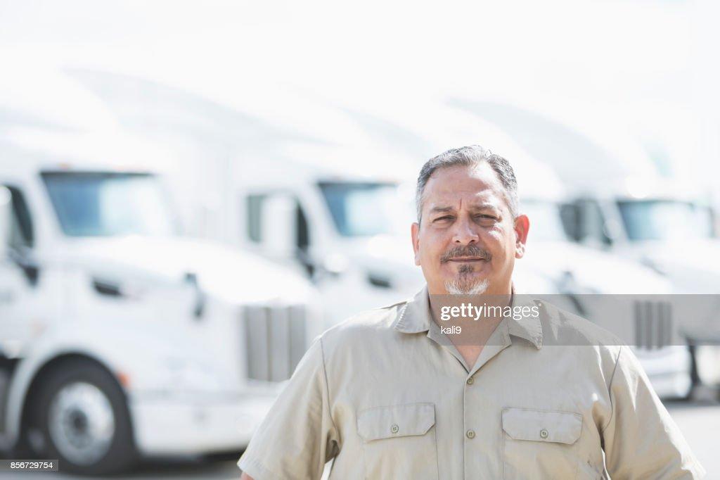 Hispanic man standing in front of semi-trucks : Stock Photo