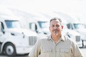 Hispanic man standing in front of semi-trucks