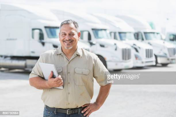 hispanic man standing in front of semi-trucks - business owner stock photos and pictures