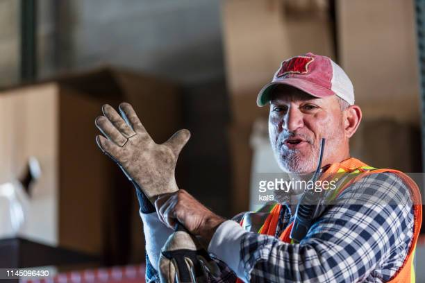 hispanic man standing in warehouse donning work gloves - work glove stock photos and pictures