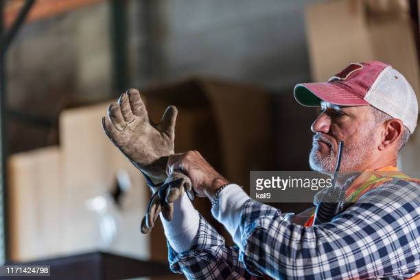 hispanic man standing in warehouse donning work gloves - work glove stock pictures, royalty-free photos & images