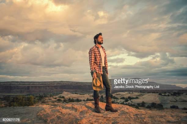 hispanic man standing on remote hilltop - cowboy stockfoto's en -beelden