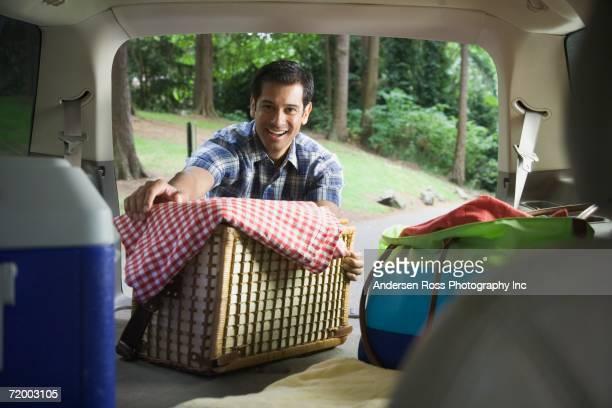 Hispanic man taking picnic basket out of back of car