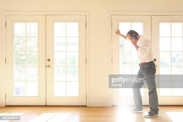 hispanic man talking on cell phone leans against french doors - french doors stock pictures, royalty-free photos & images