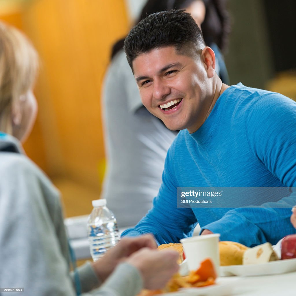 Hispanic Man Talking To Volunteer In Food Bank Soup Kitchen Stock ...