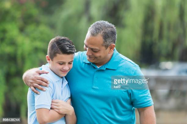 hispanic man talking with teenage son - encouragement stock pictures, royalty-free photos & images