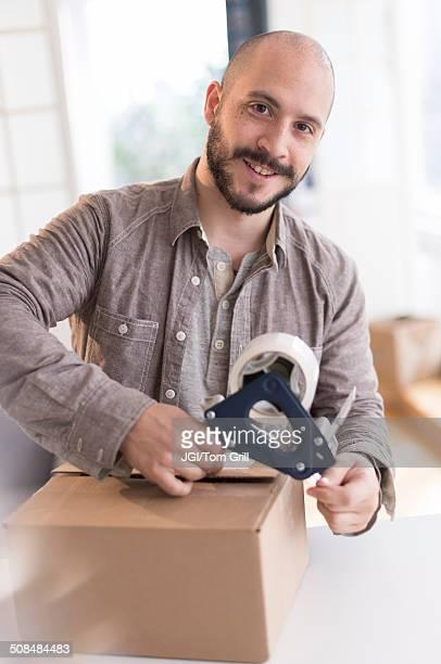 Hispanic man taping cardboard box