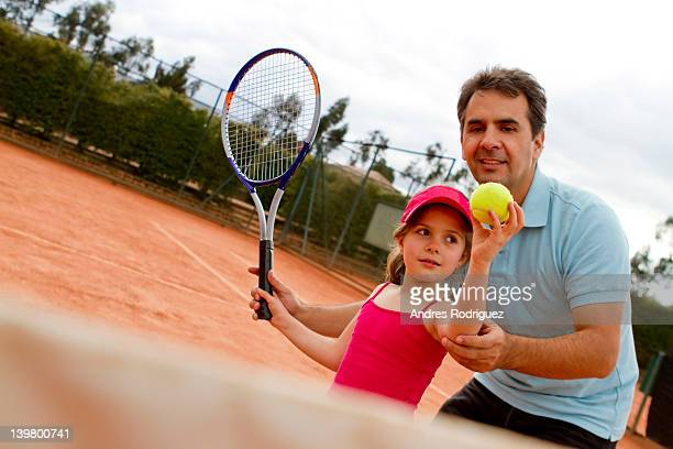 Hispanic man teaching girl to play tennis