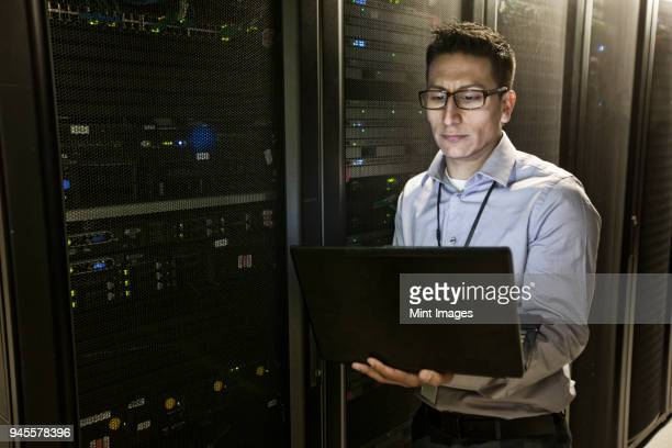 hispanic man technician doing diagnostic tests on computer servers in a large server farm. - threats stock pictures, royalty-free photos & images