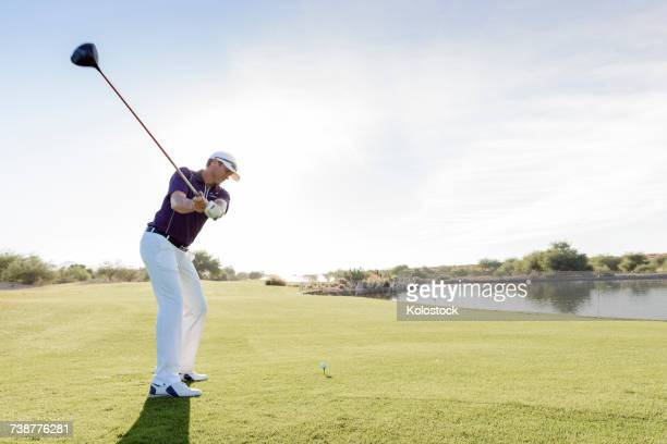Hispanic man teeing off on golf course