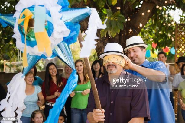 hispanic man trying to hit pinata - pinata stock pictures, royalty-free photos & images