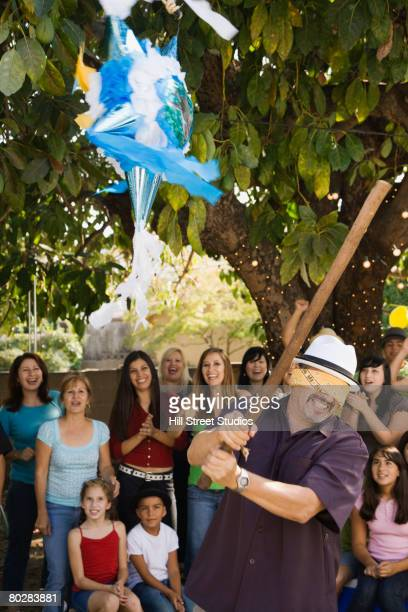 Hispanic man trying to hit pinata