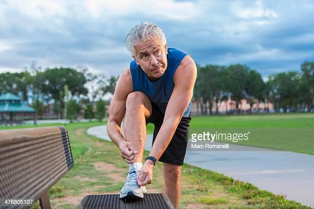 Hispanic man tying shoe in park