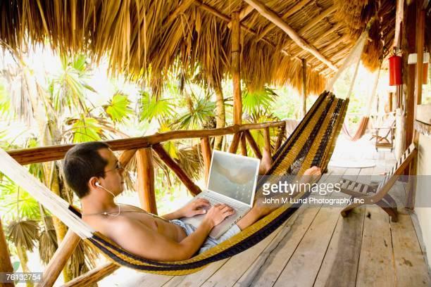 Hispanic man typing on laptop in hammock