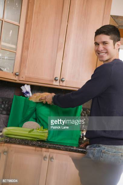 Hispanic man unloading recyclable shopping bag in kitchen