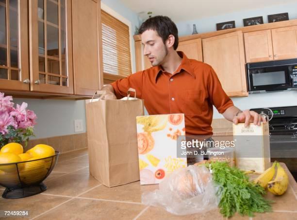 Hispanic man unpacking groceries in kitchen