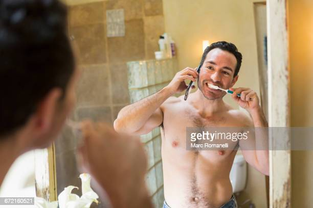 Hispanic man using cell phone and brushing teeth in mirror