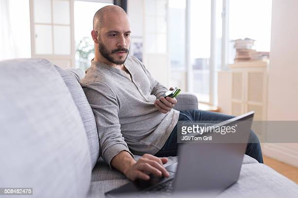 hispanic man using cell phone and laptop on sofa - recibir fotografías e imágenes de stock