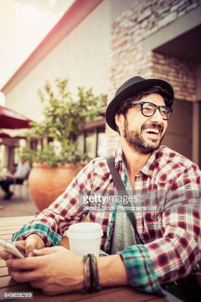 Hispanic man using cell phone at coffee shop