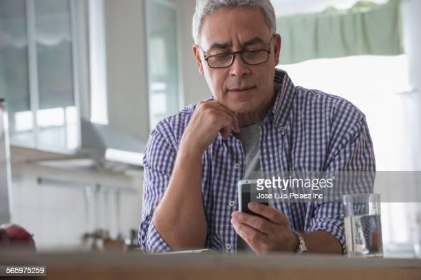 Hispanic man using cell phone in kitchen