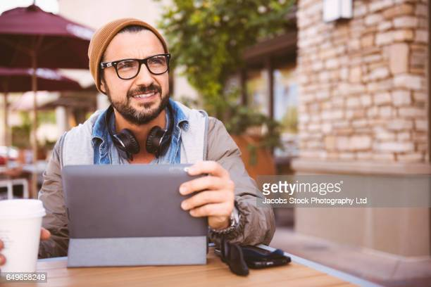 Hispanic man using digital tablet at coffee shop